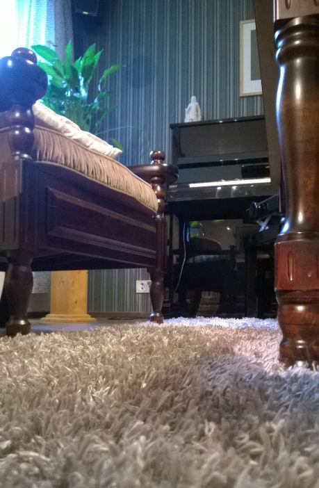 Olohuone jossa piano ja sohvakalustoa